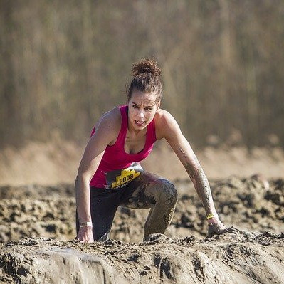 A woman athlete competing in a mud race