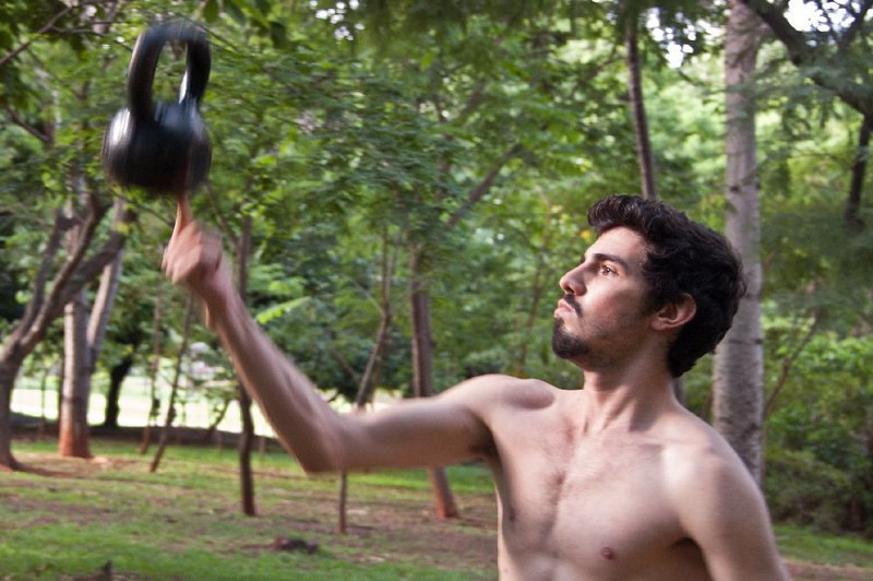 A man balancing a kettlebell on his index finger