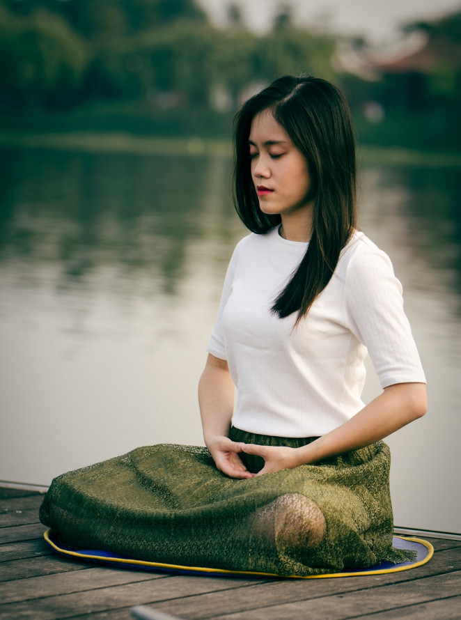 a young lady sitting on a pier by a river quietly meditating