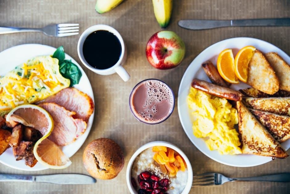 A variety of breakfast food including, meats, eggs, hash browns, breads, fruit, coffee, and porridge oats with fruit