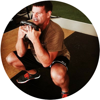 A man performing a goblet squat with a kettlebell