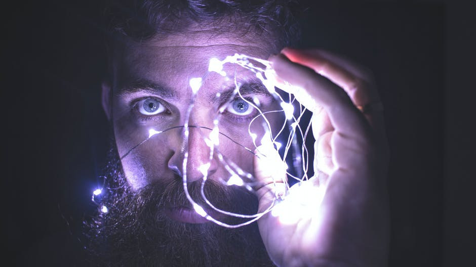 A bearded man holding his hand up and watching lights in front of his face