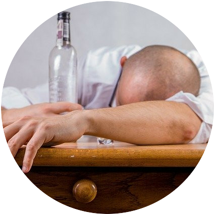 A man with his head on a table and an empty bottle next to him potentially asleep from too much to drink