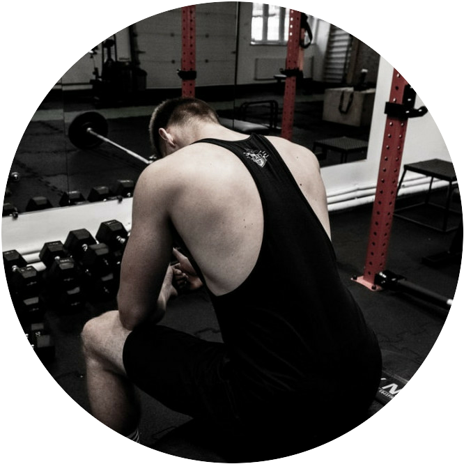 a man seated in the gym staring at the floor