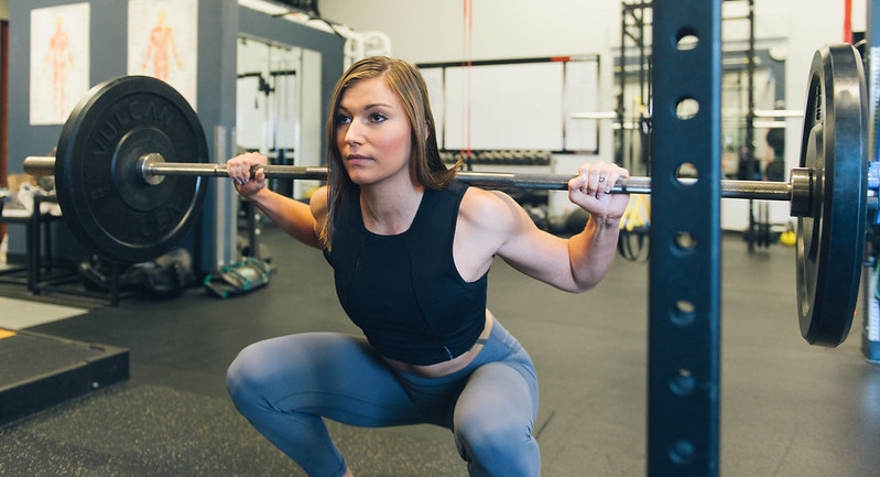 A woman performing a barbell squat in a gym