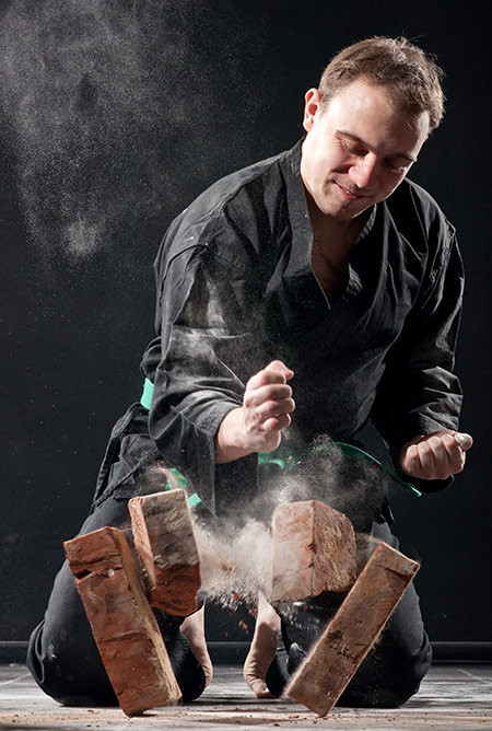 A Man Smashing a Pile of Bricks With His Bare Hands