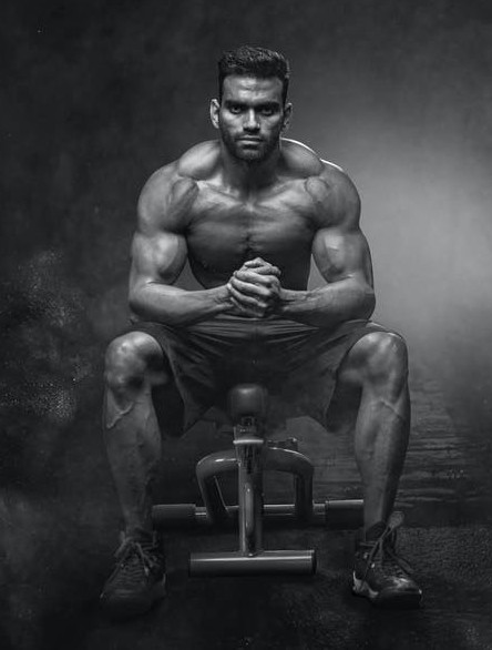 A muscular man sitting on the end on a gym bench