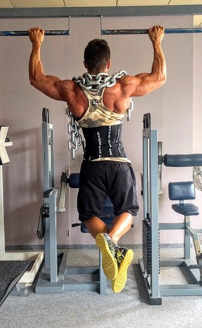 A man doing pull ups with a heavy chain over his shoulders