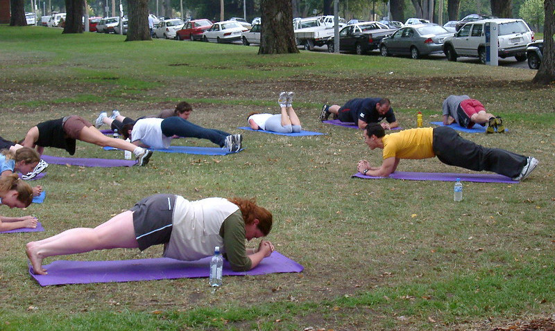 A Group of People Planking in the Park
