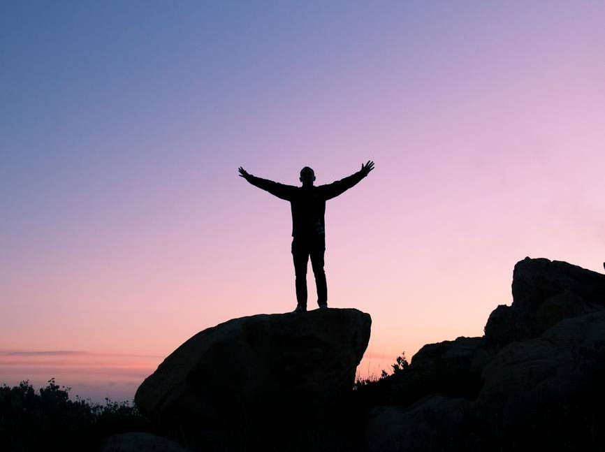 The silhouette of a person standing on a rock with their arms outstretched