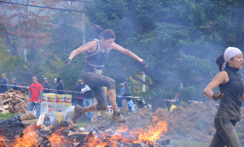 A Woman Jumping Over a Fire During The Spartan Race