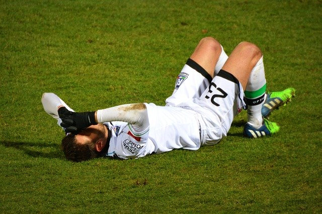A football player lying injured on the pitch