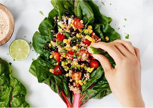 A person squeezing fresh lime juice onto a colourful salad