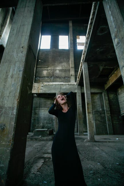A Woman In A Deserted Buidling, Holding Her Hands to Her Head, While Screaming