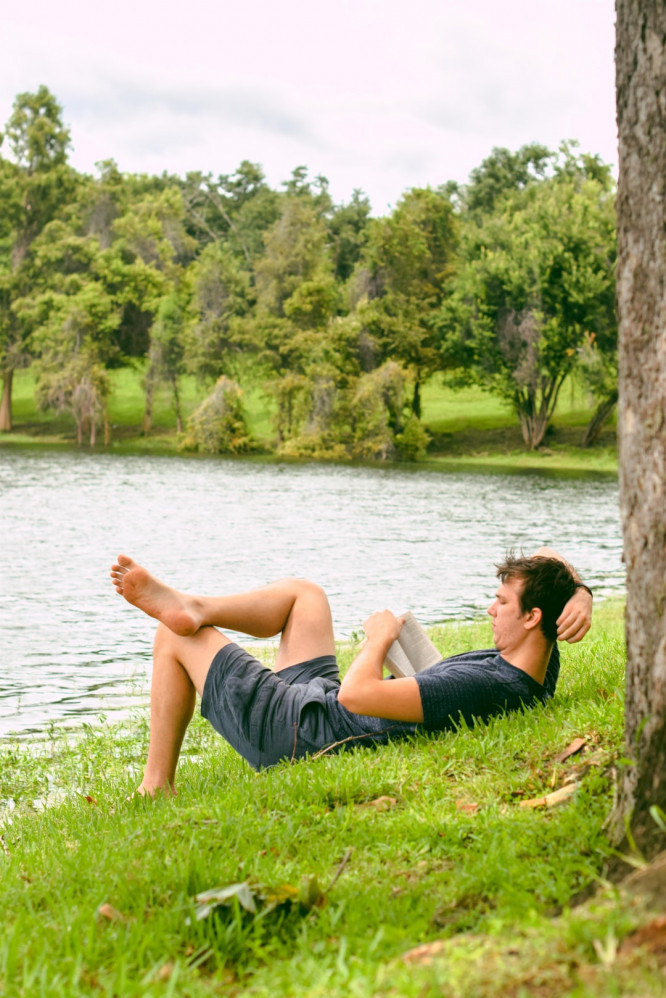 Man Relaxes On The Bank Of A River While Reading A Book