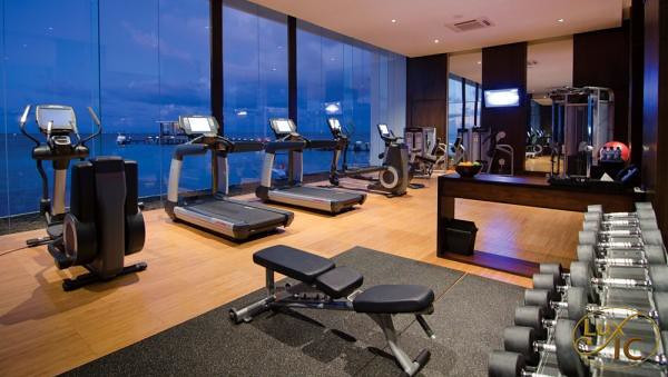 A gym featuring cardio equipment, dumbbells, and a bench