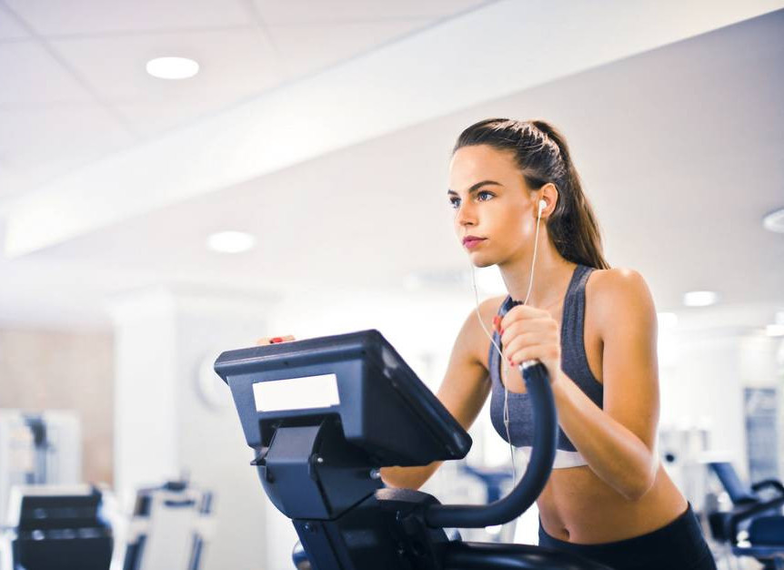 A woman exercising on an elliptical trainer
