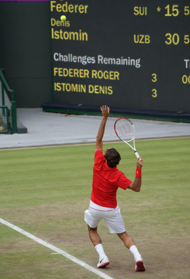 Roger Federer, the tennis player, about to serve with the scoreboard in the background