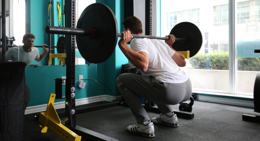 A man performing a barbell squat in front of a mirror