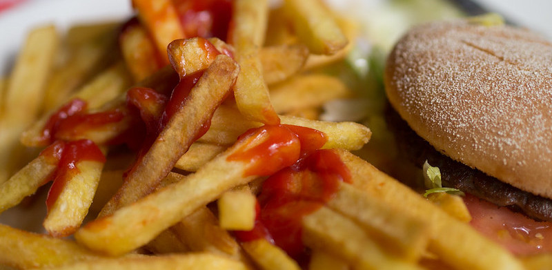 A burger with chips smoothered in tomato ketchup