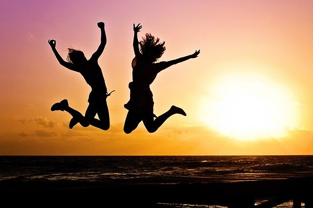 A silhouette of 2 people jumping into the air as the sun goes down