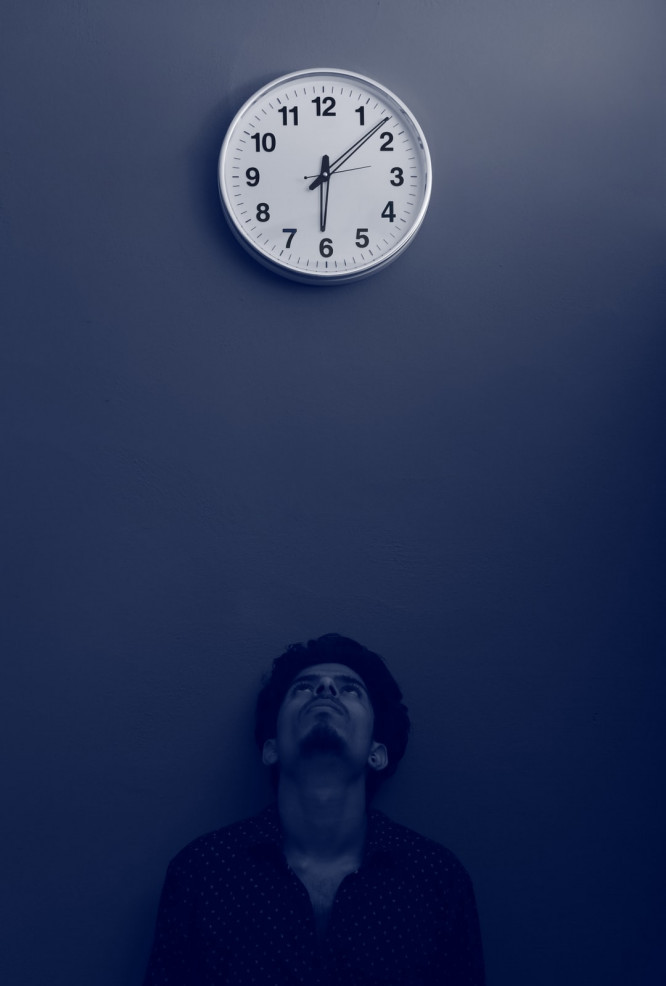 A man staring up at a clock with the time being 6.08