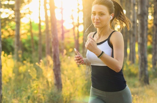 Young Woman Jogging While Holding Her Phone With Her Earphones In