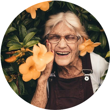 A mature woman smiling joyfully, standing among orange flowers, including wearing one in her hair