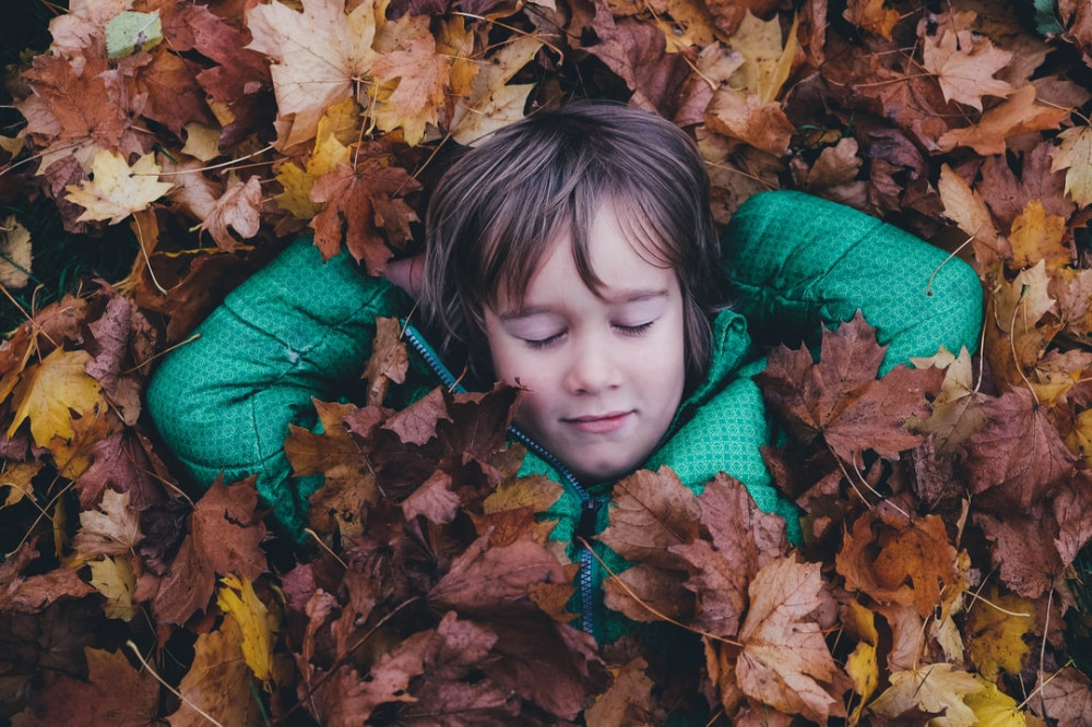 A child with their hands behind their head resting, [possibly sleeping, in a pile of leaves