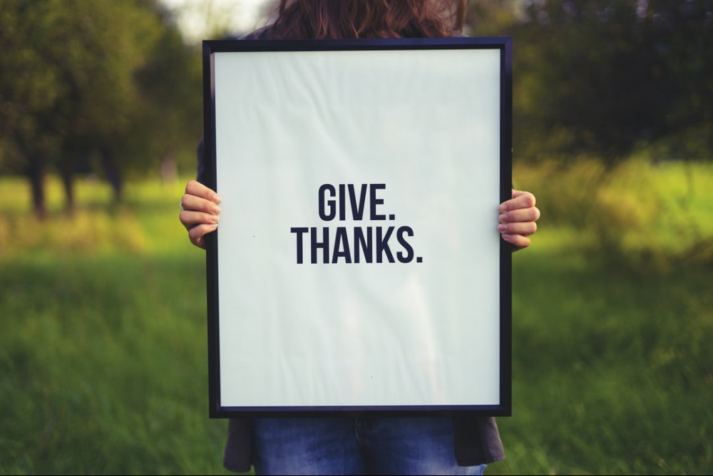 """Someone holding up a sign that says """"GIVE THANKS"""""""
