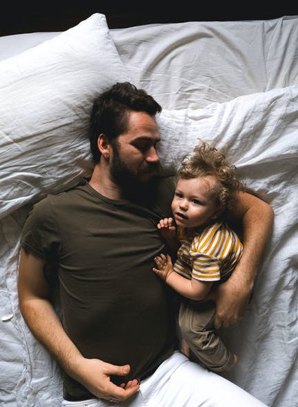 A Man Cuddling a Child in Bed