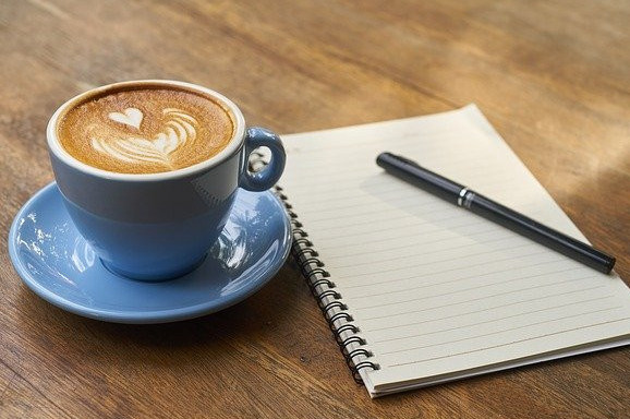 A Cup Of Coffee With A Heart Made From Frothy Milk Next to a Pad and Pen