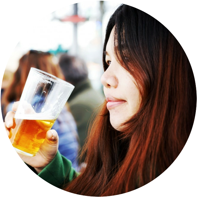 A woman drinking a glass of beer