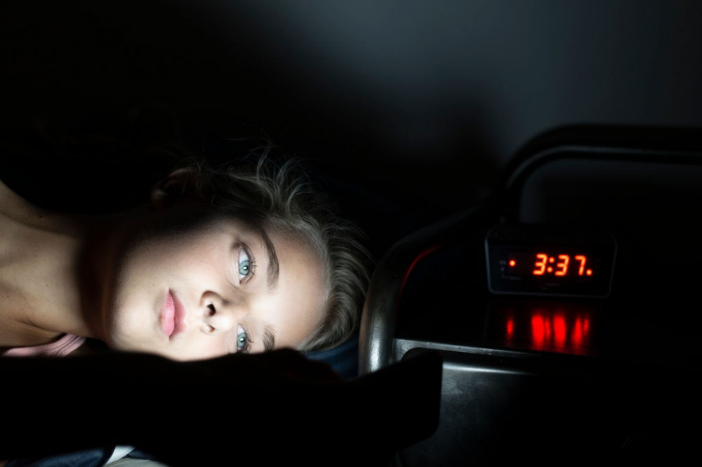 A Woman Lying in Bed Staring At a Digital Clock Which Reads 3.37