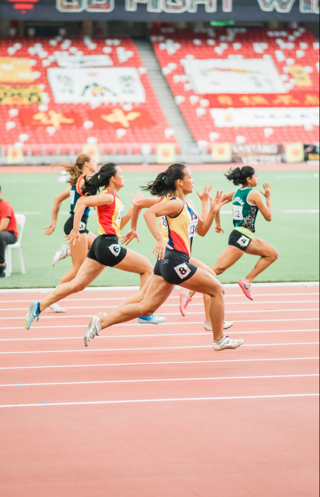 Women in a stadium sprinting on the track