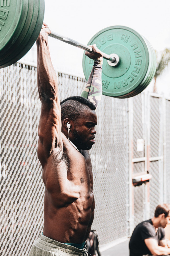 A man holding a heavy barbell above his head