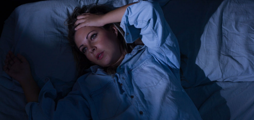Woman lying in bed holding her hand to her head unable to sleep