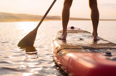 Mans Legs Standing on Paddle Board