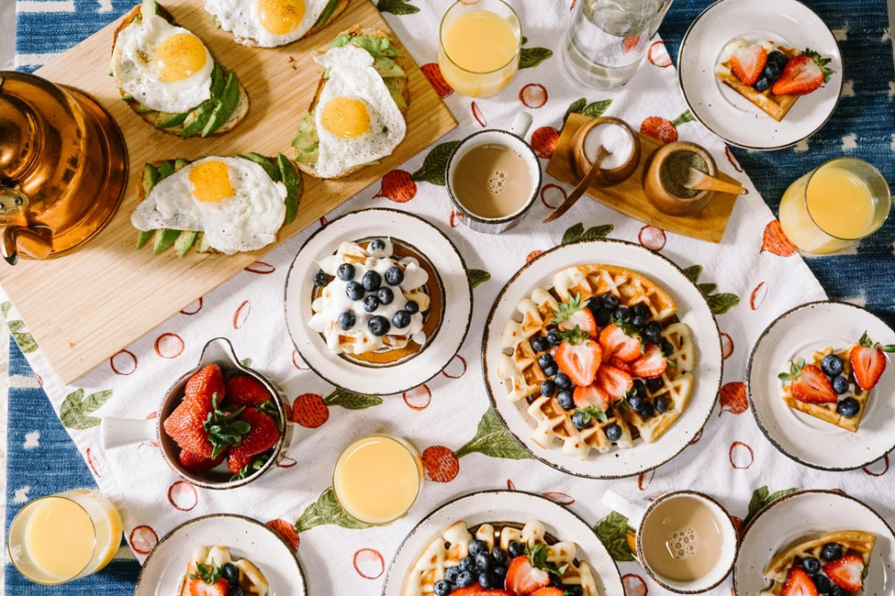 A delicious meal set on the tabel consisting of fruits, pancakes, juice, tea and eggs