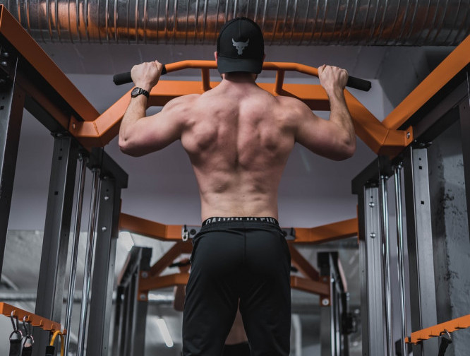 man performing pull ups for back training