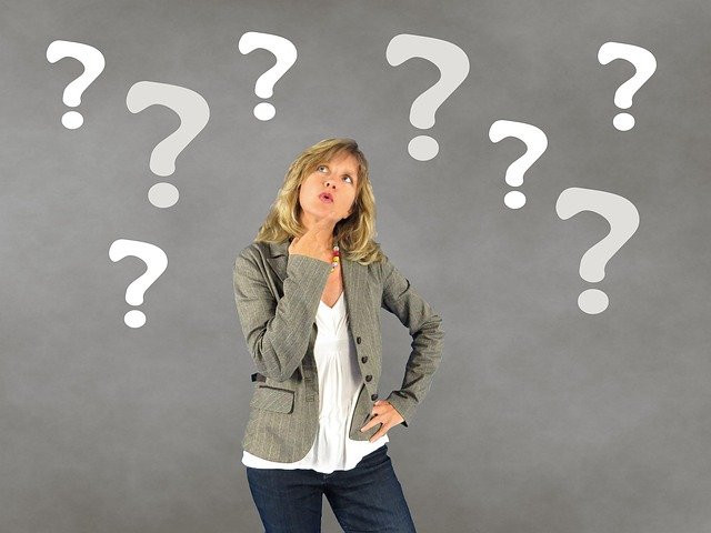 A woman standing in front of a grey background with question marks, thinking