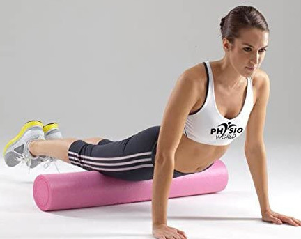 A woman in sports gear using a pink foam roller against a white background