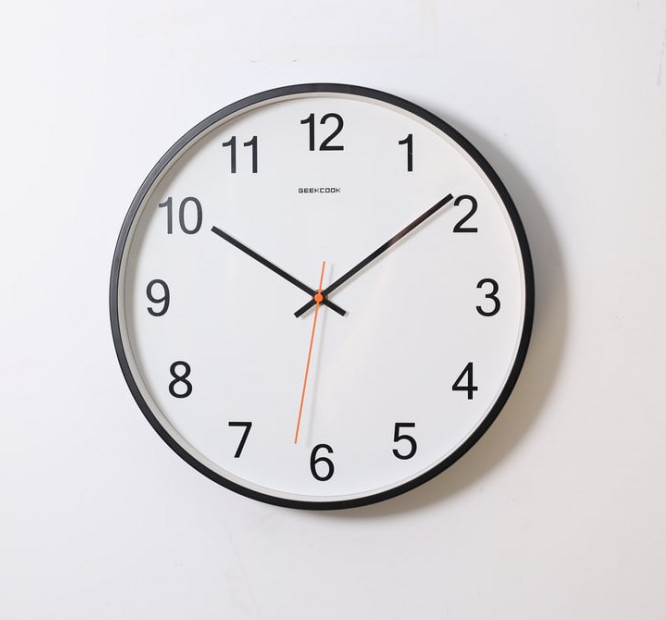 A clock with a black frame and white face on a white wall