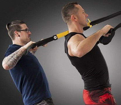 Two men leaning back whilst holding onto a black and yellow suspension trainer