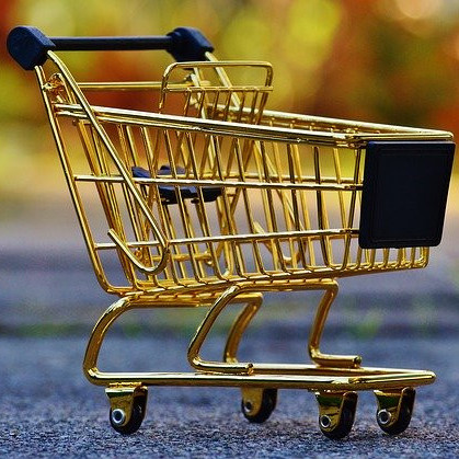 A close up of a miniature gold and black metal shopping trolley