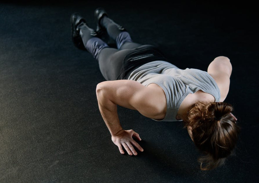 A-woman-wearing-sportswear-doing-a-push-up-on-the-floor
