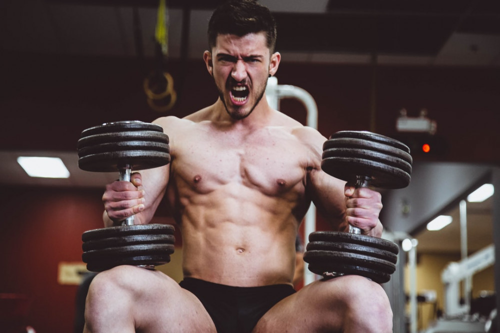Man seated with a pair of black iron dumbbells