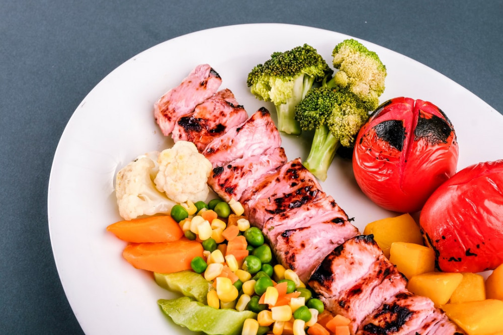 A white plate of lean meat and colourful vegetables