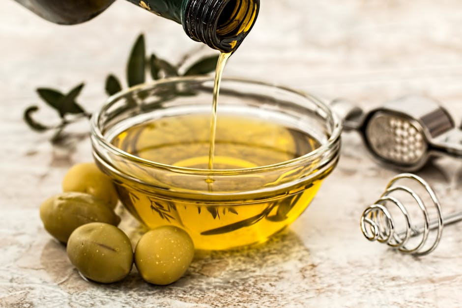 Close up of olive oil being poured into a small glass dish next to some green olives