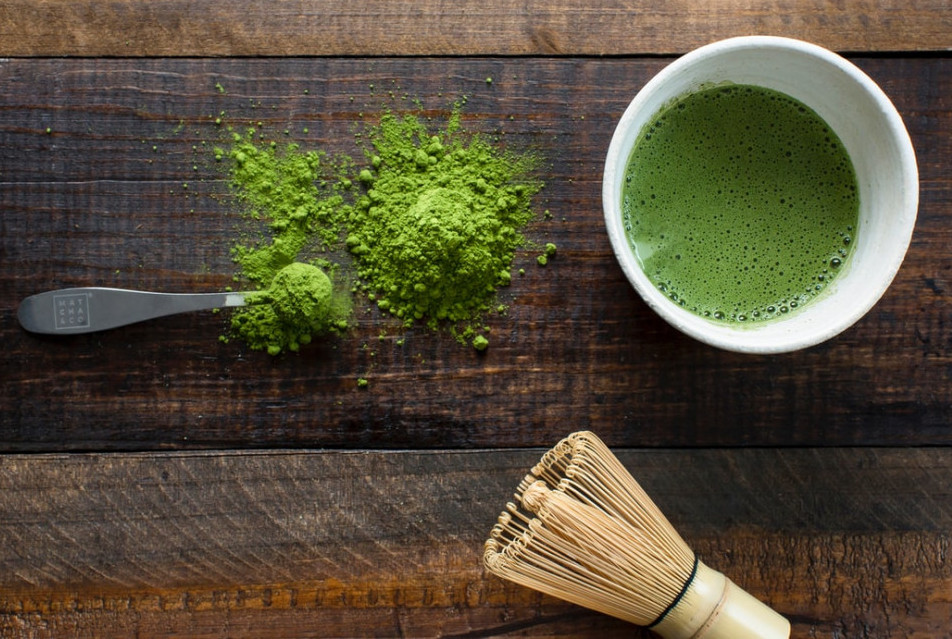 A white mug of green tea sitting next to powdered green tea on a wooden table top